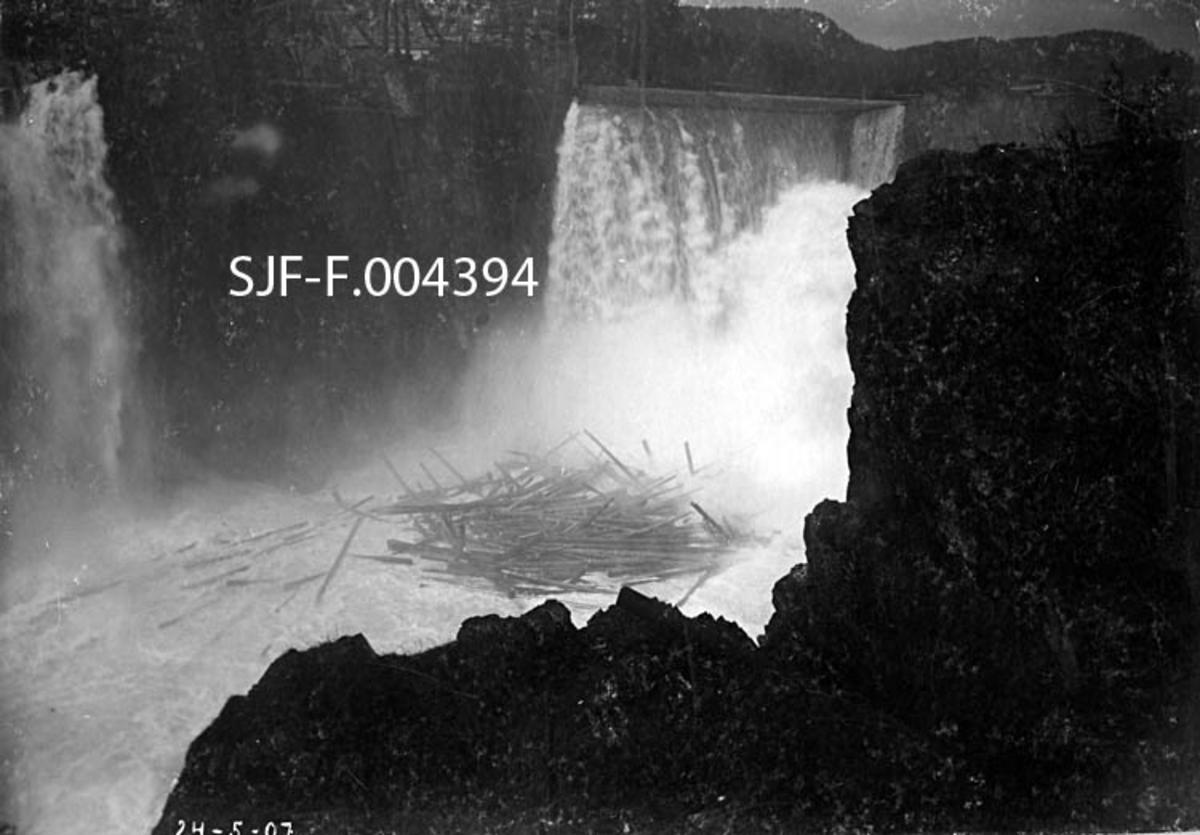 Den såkalte «Tinnfoss-sveiva» i Notodden kommune i Telemark (da dette fotografiet ble tatt var det «Hiterdal» [Heddal] kommune).  Tinnfoss-sveiva var en kraftig strømvirvel som oppsto i 1907, og som preget denne fløtingssesongen.  Dette fotografiet er tatt fra bergplatået på den østre elvebredden, ned mot en kvitskummende elva, der en betydelig mengde tømmer roterte rundt og rundt i strømvirvelen, der vann fra østre og vestre fosseløp møttes.  Bakgrunnen for at dette fenomenet oppsto og konsekvensene det fikk var det delte meninger om.  Administrasjonen og generalforsamlinga i Skiensvassdragets Fellesfløtningensforening pekte på arbeider Tinfos Papirfabrik hadde fått utført foregående vinter. Fabrikken hadde sitt vanninntak ovenfor det vestre fosseløpet.  Der hadde det et par tiår vært en provisorisk tredam, som ble revet og erstattet av en betongdam nærmere fossestupet.  Samtidig ble det vekksprengt bortimot 3 000 kubikkmeter med fjell for å utvide vanninntaket.  Mye av massen fra denne sprenginga ble tippet i fossen.  Representantene for Fellesfløtningsforeningen mente at dette var årsakene til at Tinnfoss-sveiva oppsto.  Også når det gjaldt effekten av sveiva var meningene delte.  Fløtingsinteressene hevdet at strømvirvelen og steinmassene under fossen bidro til omfattende tømmerbrekkasjer, sprekkdannelser i rotendene på tømmerstokkene og omfattende slitasje på yteveden.  Advokaten til Tinfos Papirfabrik framholdt at omfanget av skadene var sterkt overdrevet, og at mange av skadene hadde oppstått på andre steder i vassdraget.  Fløtinga i Tinnåa i 1907 foregikk i to perioder, fra 14—15. mai til 1. juni og fra 15. juni og framover.  Grunnen til at aktiviteten opphørte i to uker var de omfattende skadene, og håpet om at dette problemet kunne reduseres om en seinere fikk større vannføring.  Det viste seg at fløtinga gikk mye lettere og at skadeomfanget ble langt mer moderat under «2. brøtningstur», antakelig fordi kreftene i det vårstore vassdraget i mellomtida hadde