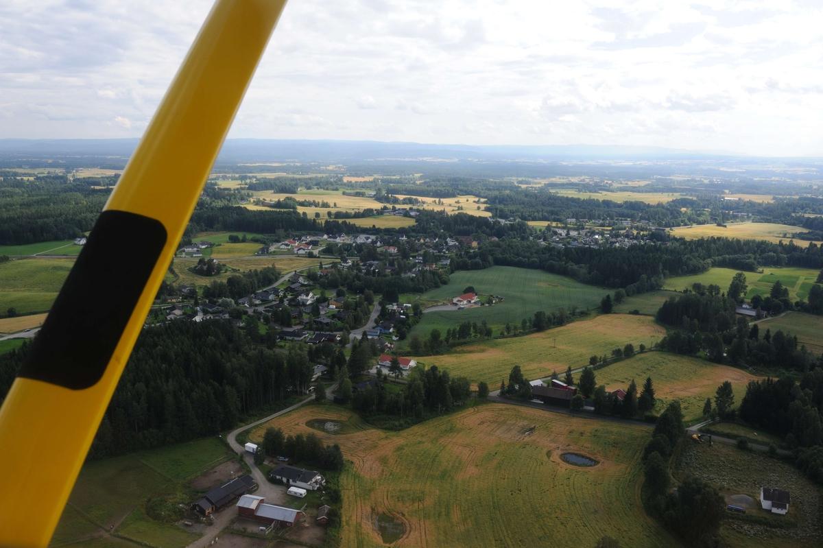 Flyfoto. Luftfoto utført i forbindelse med Vangsboka. Gårder i Vang, samt noe Hamar by fra lufta.