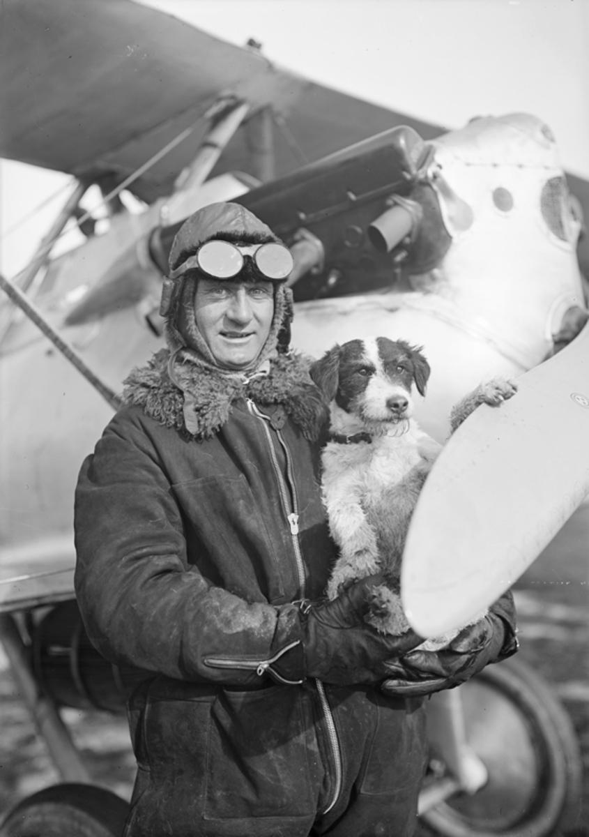 Porträtt av Einar Lundborg med hund framför flygplan J 2 på Malmen.