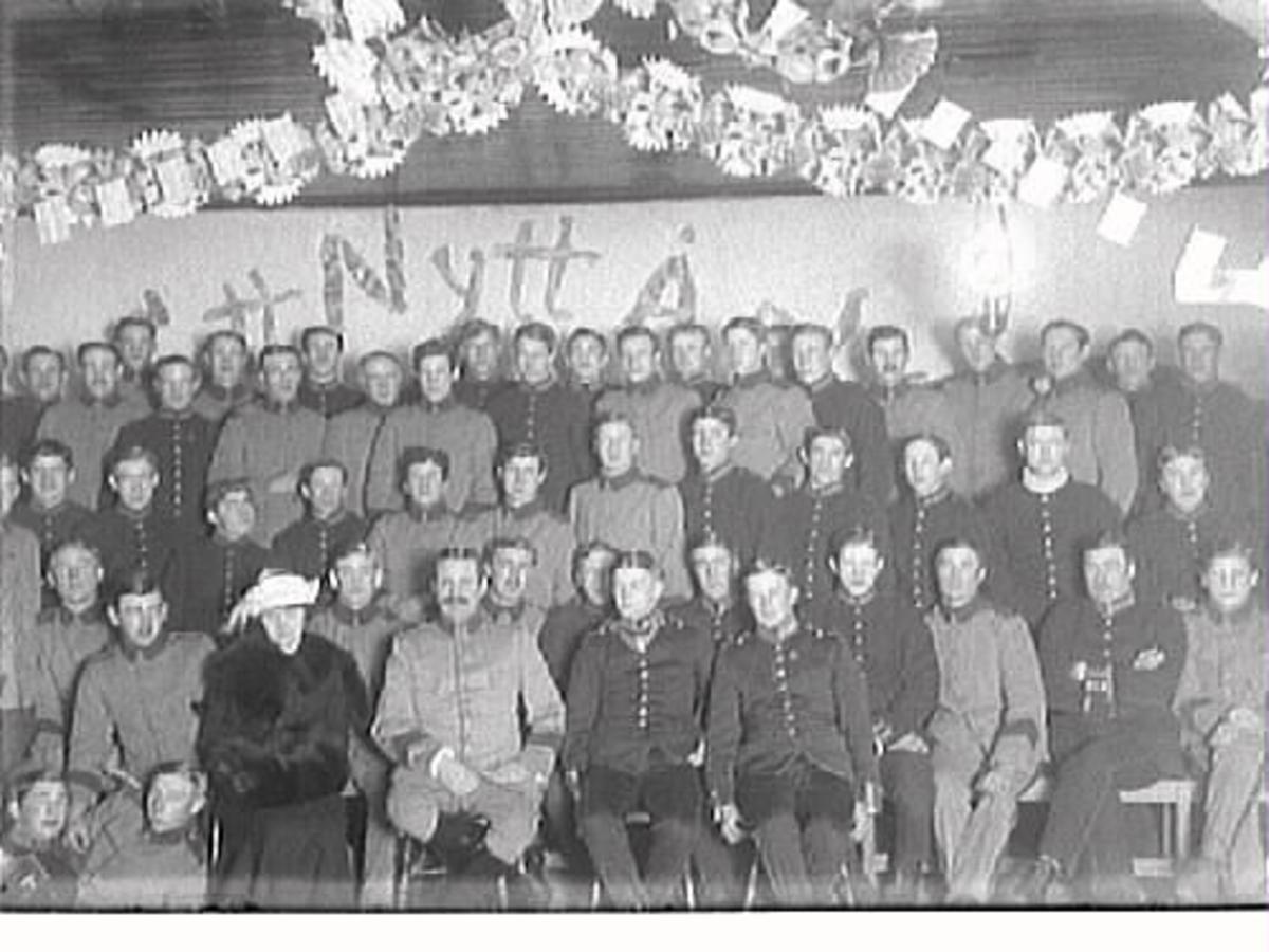 Nyårsfest på fästningen. Militärer, klädda i olika typer av uniformer. På den främre raden sitter en kvinna. Hon har pälsmuff och pälsboa. Vid hennes sida en stram man med mustach (maken?)