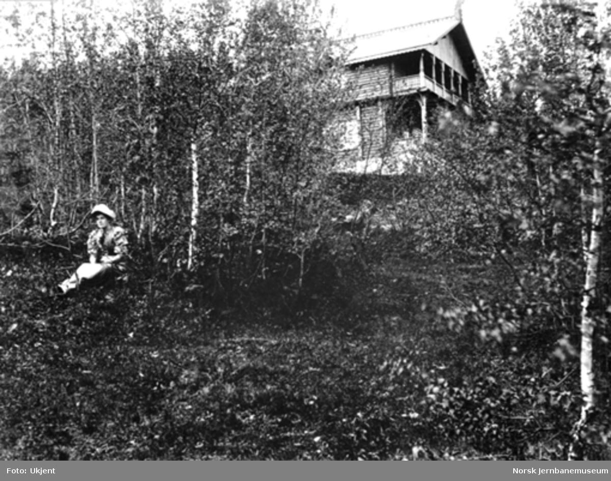 En kvinne med en villa i sveitserstil i bakgrunnen
