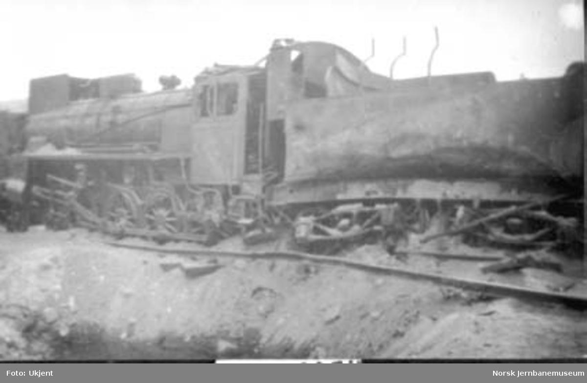 Damplokomotiv type 26c nr. 437 skadet etter bombenedslag kloss inntil sporet på Lesja
