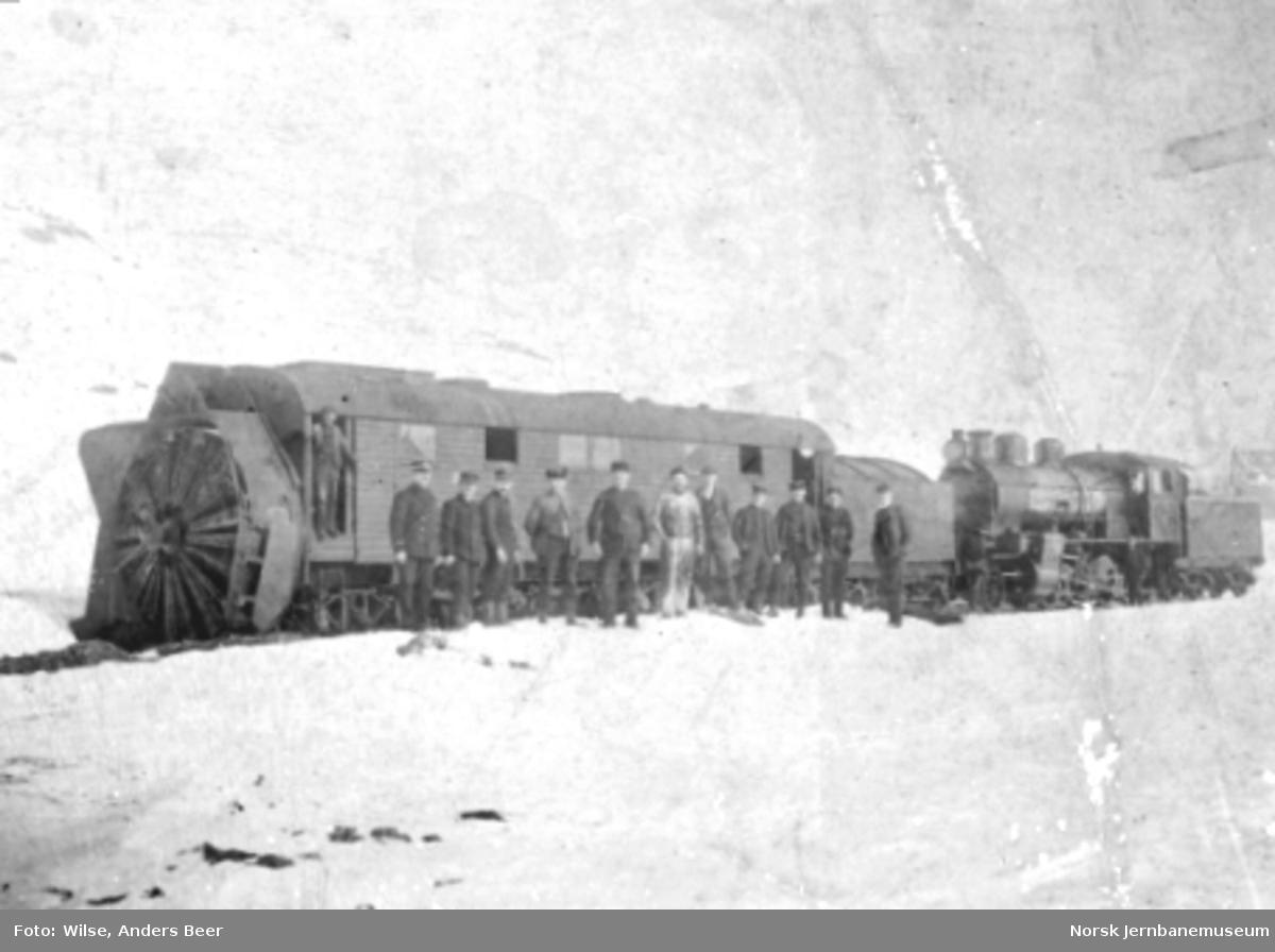 Roterende snøplog foran et damplokomotiv av type 22a med personalet oppstilt foran