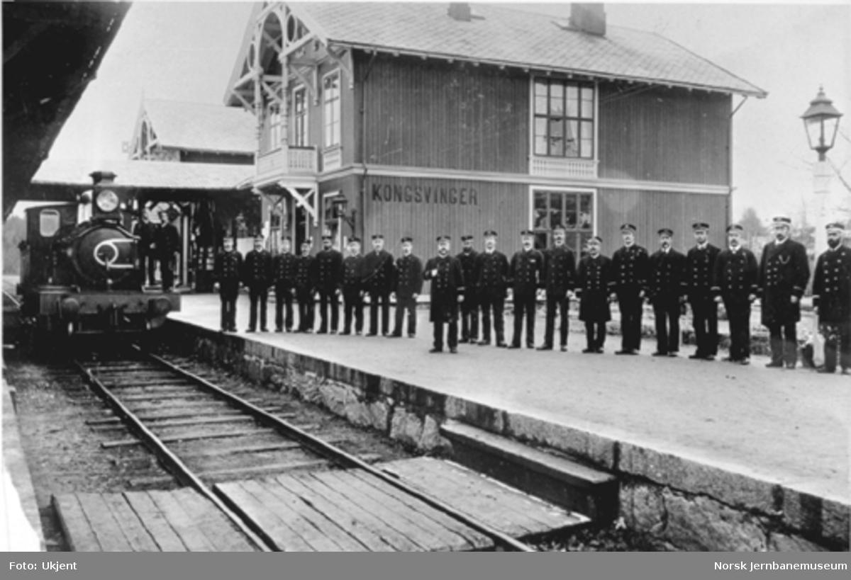 Personalet på Kongsvinger stasjon oppstilt foran stasjonsbygningen og med et damplokomotiv i spor 1