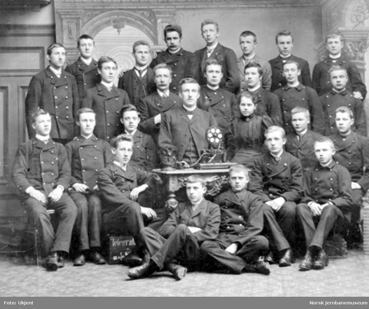 Gruppebilde med telegrafistelever bak et bord med telegrafiapparater