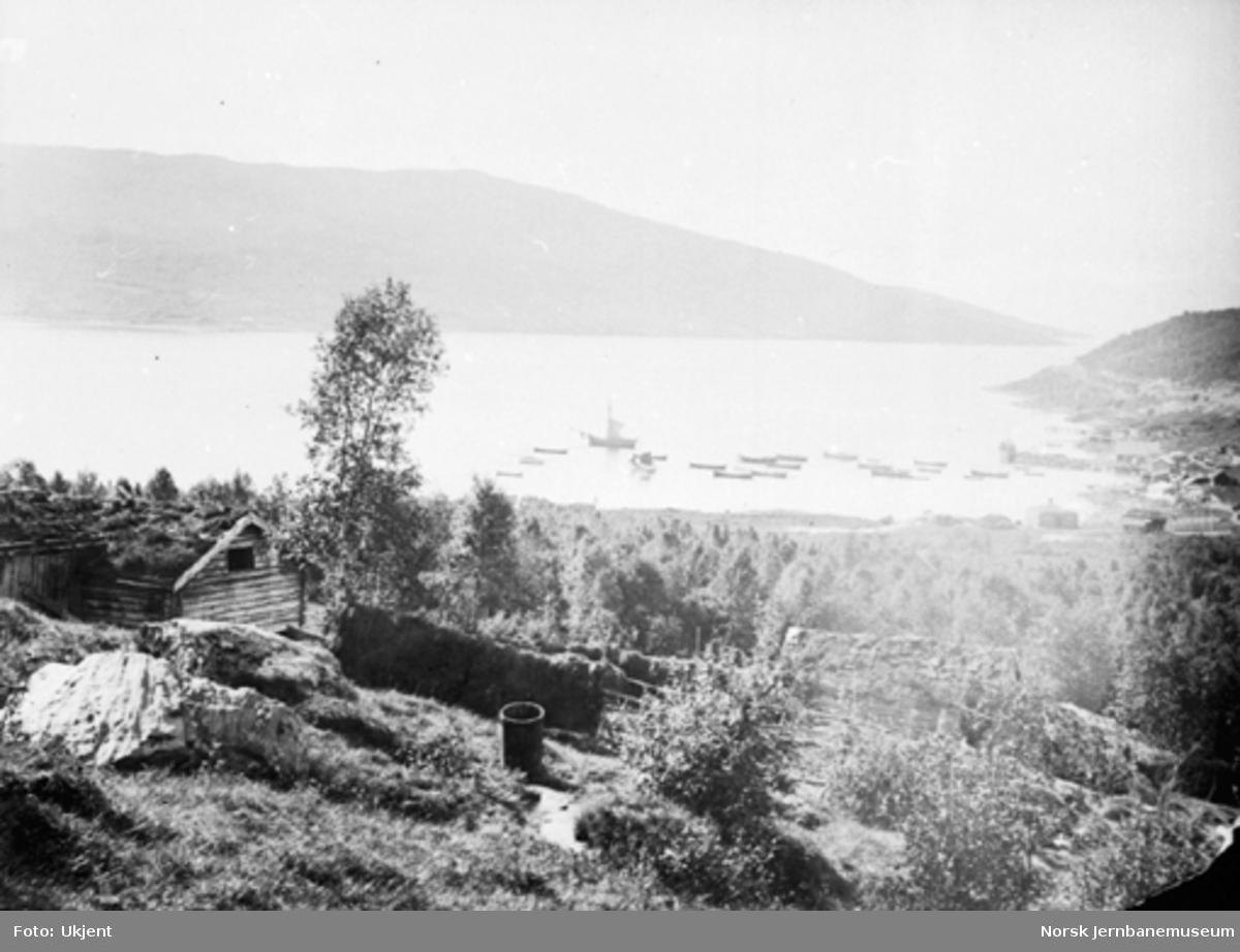 Oversiktsbilde fra Narvik med båter på vågen og et bruk med hesjer i forgrunnen