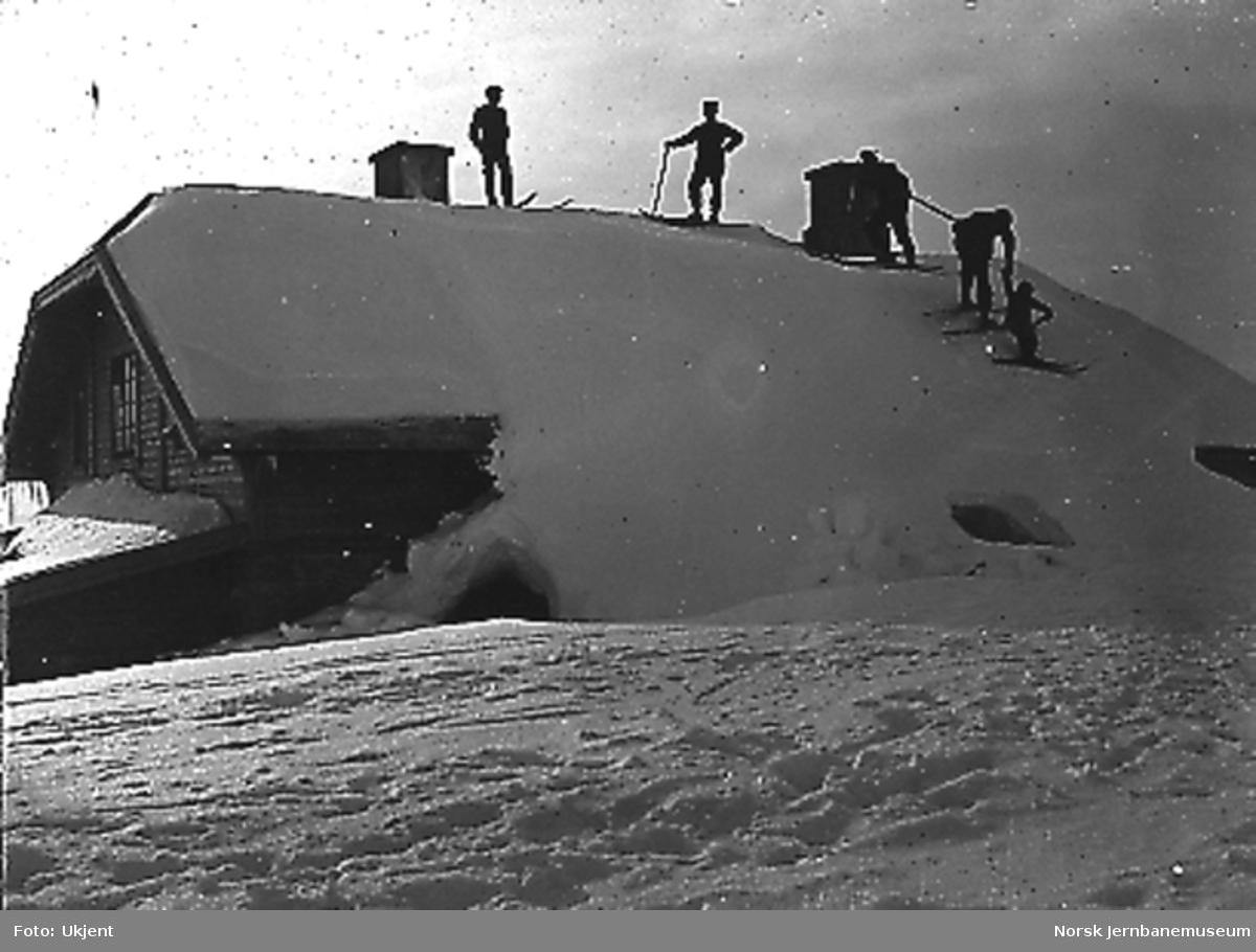 Fem mann på ski på taket av Fagernut vokterbolig