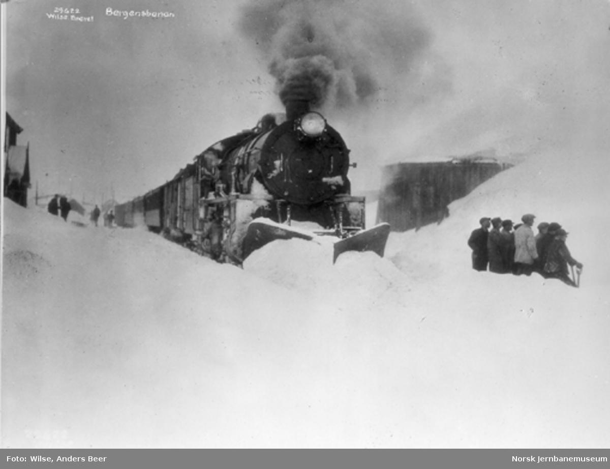 Damplokomotiv type 31b med stor frontplog foran østgående persontog på Finse stasjon : en gjeng snømåkere til høyre i bildet