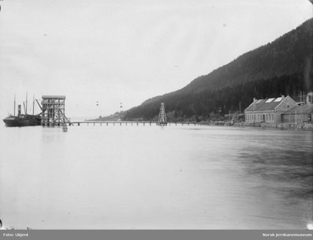 """Thamshavn omformerstasjon og verksted samt malmlastekaien med taubane; ved kaien det første malmlasteskipet """"Aira"""" oktober 1909"""