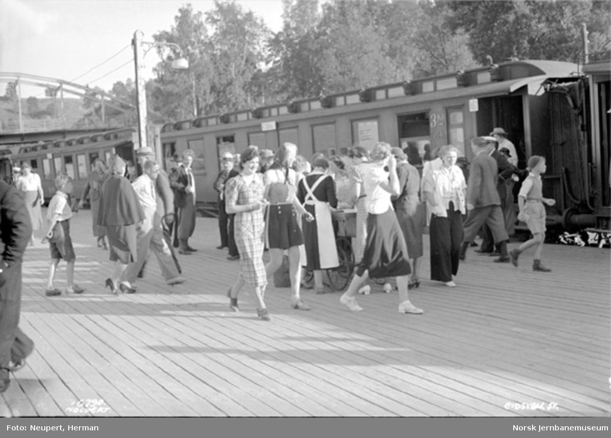 Eidsvoll stasjon med mange reisende foran et fjerntog; servering på plattformen