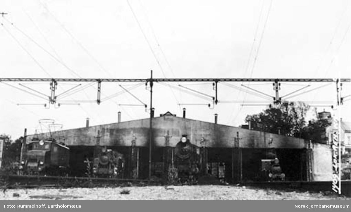Drammenbanens elektrifisering : ledningsoppheng ved lokstallen Filipstad med både normal- og smalsporede lokomotiver foran stallen