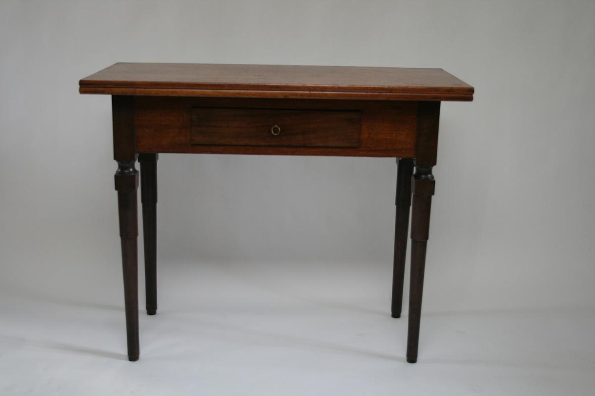 Spillebord i mahogni, med en skuff i sargen og plate til å slå ut. Plata ligget løst på sargen.