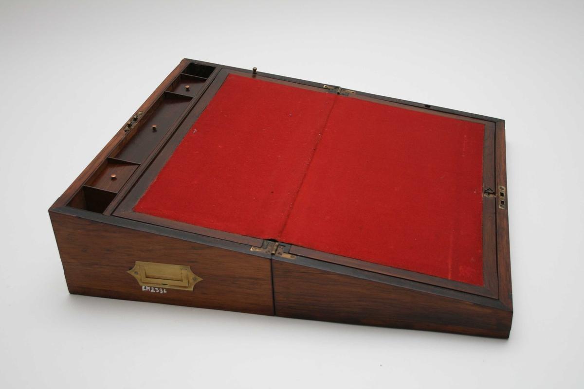 Form: Rektangulært Skrinet har også fungert som skrivebord i åpnet og utslått tilstand.  Skriveklaffen er trukket med rød filt Det har 5 små rom - tre av dem med lokk som har messingknopp - og to store rom.  I tillegg er der en skuff underst som åpnes fra siden.