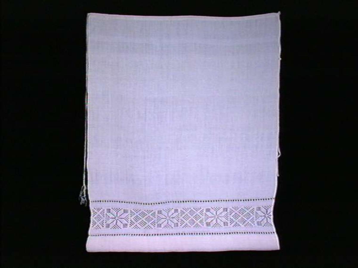 Hvit forkle med dekor i hvitt broderi.