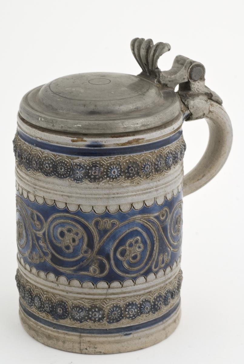 """Krus i grå keramikk med lokk av tinn, av en type som stammer fra Westerwald-området i Rhinland. Karakteristisk for slike krus er risset og stemplet dekor og pålagte relieffer, farget med koboltblått og senere også manganfiolett, under klar saltglasur. Slike lave, sylinderformete krus kalles på tysk """"Humpen"""" og ble masseprodusert gjennom hele 1600- og 1700-tallet. Ref: Albert Steen: Kanner og krukker fra Køln til Koblenz, i: Om kunstindustri, Trhm. 1991"""