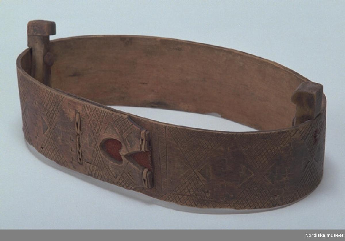 """Inventering Sesam 1997-1998: L 25, B 14, H 8,5 cm Ask, oval, svepäska. Botten- och lockskivor saknas. Svepet av lövträ, med rester av trädymlingar vid nederkanten. Hopfästning av svepet med rottågor, kedjesöm, två rader. Utskurna ståndare av lövträ, den ena fjädrande, fästade på svepets insida med spikar av järn. Svepet målat i brunt, med skurna och ristade rutmönster. På svepets hopfästning skuren, genombruten dekor i hjärtform, mellan svepändarna ett rött ylletyg. Med blyerts skrivet på svepets insida """" Anses för 200 år gammal """". /Agnetha Blomberg 1997"""