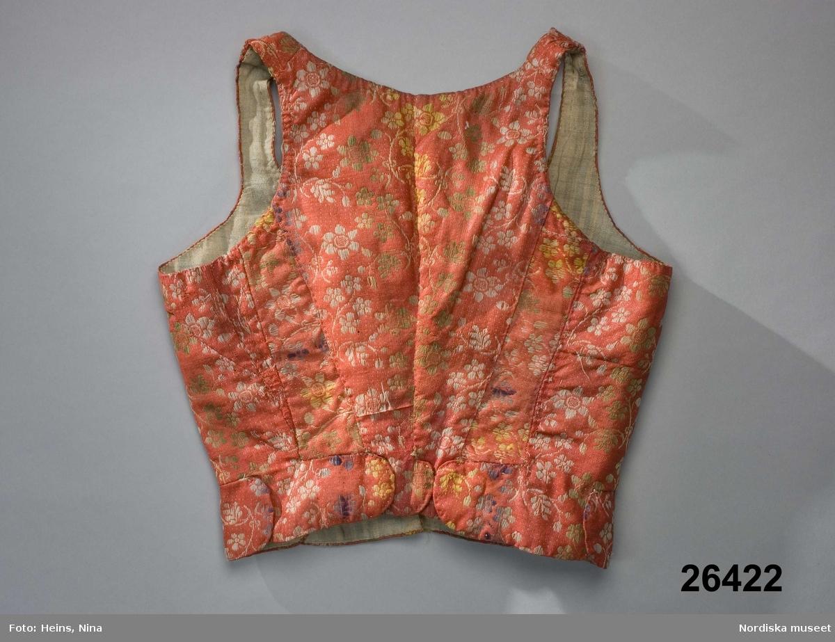 Livstycke av fint kamgarnsylletyg med stark glättning, botten röd i tuskaft med blomränder och småprickig botten i schatterande färger av  blått, grönt, gult samt vitt genom extra mönstervarp. Tyget kallas taborett eller brilliant, se prov i A. Berchs samling från mitten av 1700-talet. 2 framstycken/sidstycken med flera skarvbitar mot ryggen och under vänster armhål, 2 smala ryggstycken som går ned i 2 njurformade skörtflikar, likadana rundade skörtflikar även på framstycken och sidstycken, allt som allt 8 skörtflikar som överlappar varandra. Snörning med  8 par snörhål sydda med vitt lingarn. Foder av  ljusblå-och vitrutigt linnelärft samt i sidorna iskarvat med grov oblekt linnelärft. I midjan ett 18 mm brett linneband fastsytt på några punkter i fodret. Anges som brudlivstycke vilket säkert är riktigt men knappast från 1690, som uppgivits. Detta slags tyg vävdes speciellt i Norwich i England och började inte exporteras till övriga Europa förrän i mitten av 1700-talet. Det blev modernt i det folkliga dräktskicket under 1700-talets andra del sannolikt som en ersättning för mönstrat siden. Det var just som finaste högtidsplagg det användes eftersom det var ett dyrt köpetyg. Livstycket som det ser ut nu är sannolikt omsytt av ett äldre i 1700-talsmodell med längre skört /Berit Eldvik 2007-12-14