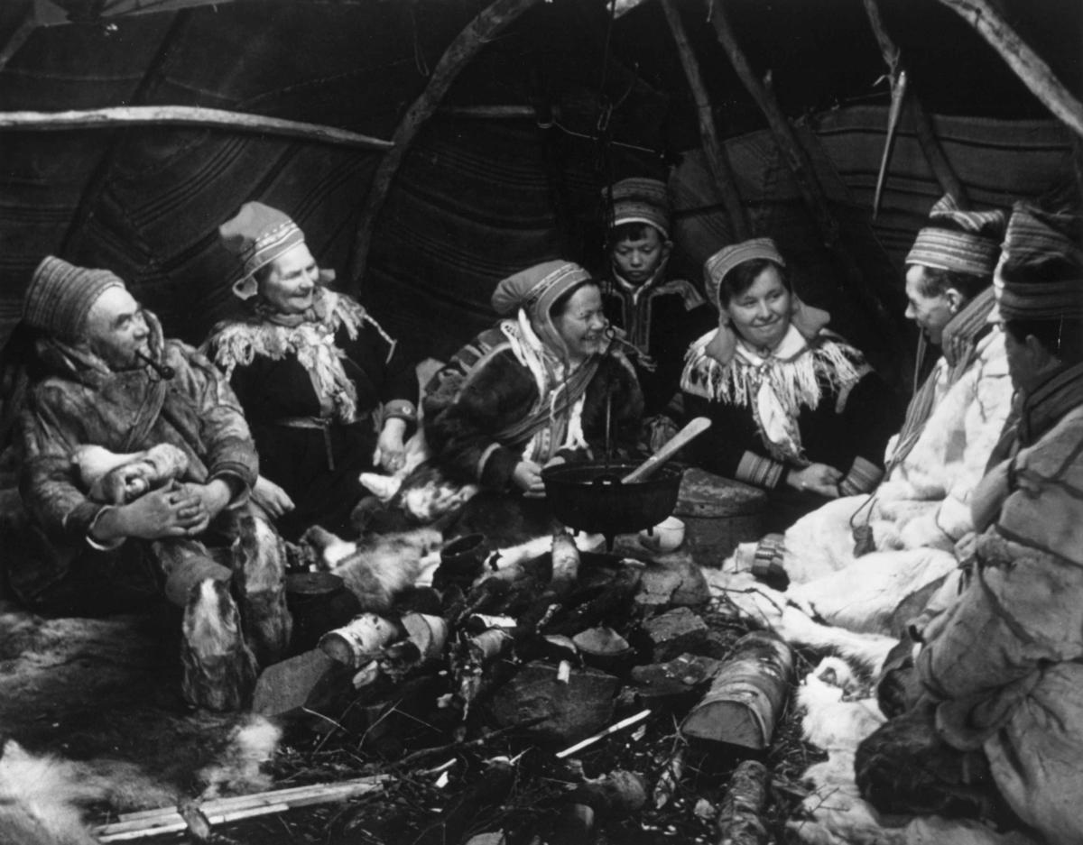 """Telt-interiør. Kautokeinosamer samlet ved ildstedet med en gryte over. Fra filmen """"Same Jakki"""" 1957 av Per Høst. Finnmark."""