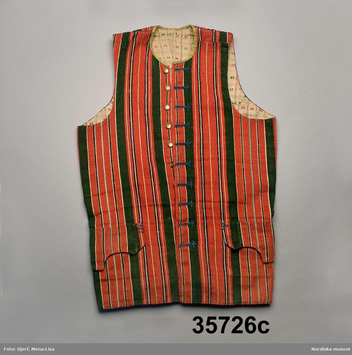 """Huvudliggaren (år 1883): """"35.726 Brudgumsdräkt fr. Toarps sn. Ås hd. Västergötland. a. Blå långrock, med broderi i silke. b. Röd toppmössa; till mössan hör en tofs i toppen. c. Väst, troligen begagnad som tröja. d. Blå knäbyxor. e. Strumpeband. Till banden höra runda tofsar. 'Dräkten är från början af detta århundrade.'; Se bref från Södermark 21/5 1883. a. Maläten. d. Maläten. e. Maläten. 'I dräkten saknas: strumpor, hvita eller blå, skor, helst med spännen, bomullshalsduk, skjorta.' Se bref från Södermark af den 22/5 1883. G. af handlanden Oscar Vennberg i Borås genom lant [?]kamrer I.A. Södermark i Borås 23/5 1883. Bil. Södermark.""""  b. Toppluva, stickad av rött ullgarn i slätstickning i ett med fodret av vitt ullgarn. Toppigheten bildas genom jämnt fördelade intagningar."""